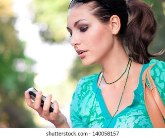 Beautiful woman talking on cellular telephone outdoor