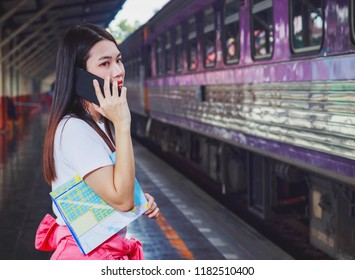 Beautiful woman talking on the phone while waiting for the train at the train station.