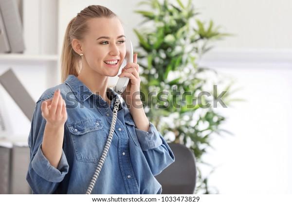 Beautiful woman talking on phone indoors