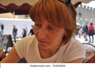 Beautiful woman tasting iced coffee in cafe in Pisa, Italy.
