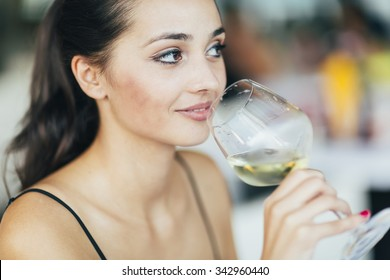 Beautiful woman tasting wine while sitting in restaurant