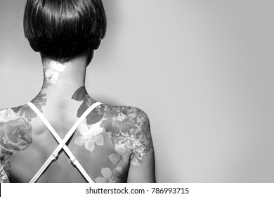 Beautiful woman with tattoo on her back, black and white and copy space