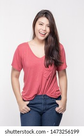 Beautiful woman teens Asia Pointing Laughing Red in t-shirt looking and pointing away with thumb over White background bright
