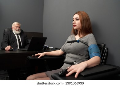 Beautiful woman at testing in grey room with polygraph. Young woman sitting in chair, to hands and body attached sensor and wire. Elderly man looking at computer polygraph.