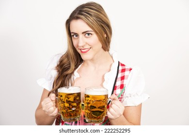 Beautiful woman in tirol dirndl dress holding a big glass of beer in her hands against a white wall.