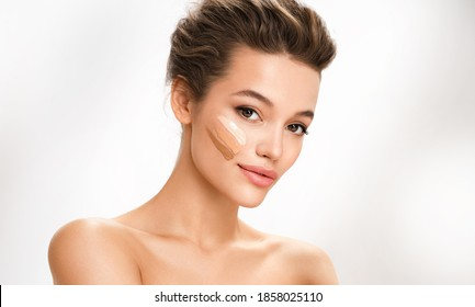 Beautiful woman with tone cream lines on her face. Photo of brunette woman with perfect makeup on white background. Skin care concept