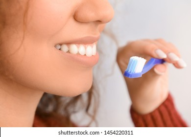 Beautiful woman with toothbrush on grey background, closeup