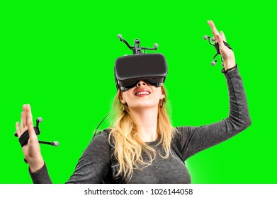 Beautiful woman touching air during  VR experience isolated on green hromakey. She wearing Virtual reality glasses or goggles, processor inbackpack on back and sensors for tracking on head and hands