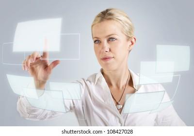 Beautiful woman touching a digital screen, panel, hologram