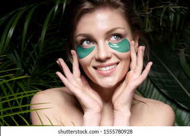 Beautiful woman touching green beauty patches and use special cosmetological utensils to keep dermis fresh. Skincare concept