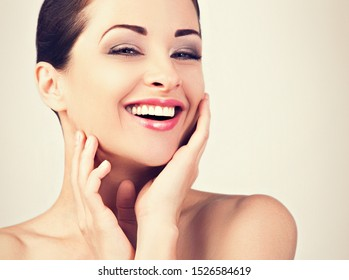 Beautiful woman touching her face skin. Laughing natural model with perfect toothy smiling. Beauty and anti aging treatment and stomatology. Closeup face portrait