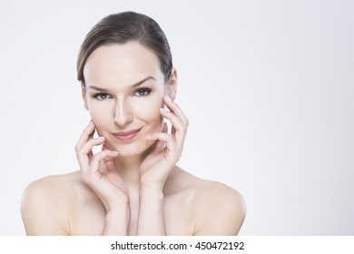 Beautiful woman touching her face, standing on a light background