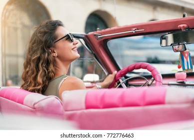 Beautiful woman tourist enjoying vacation holidays in Cuba driving a classic car.