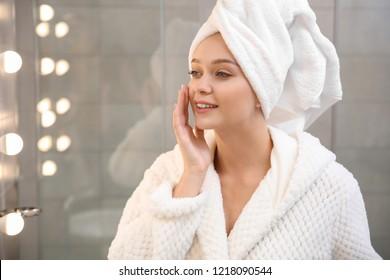 Beautiful woman with towel on head near mirror in bathroom