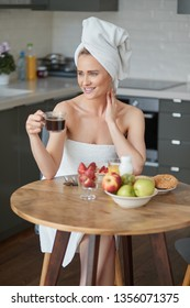 Beautiful woman with towel on head. Sitting next to table in her kitchen, having a healthy breakfast and coffee