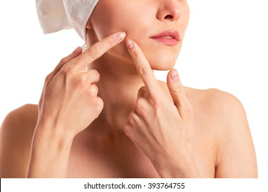 Beautiful woman with a towel on her head is squeezing pimples on her face, isolated on a white background, cropped