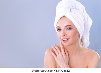 Beautiful woman with a towel on his head on a gray background