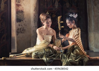 Beautiful woman in traditional dress costume playing treble fiddle. Treble fiddle or soprano sounded string Thai music instrument.