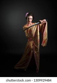 Beautiful woman in traditional Japanese  kimono with katana. Attractive woman with Japanishe sword katana.