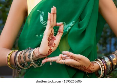 Beautiful woman in traditional Muslim Indian wedding green sari dress costume with henna tattoo jewelry and bracelets do hands nritta odissi Samyuta hastas dance Movement araala Concept background