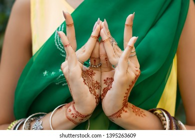 Beautiful woman in traditional Muslim Indian wedding green sari dress with henna tattoo jewelry bracelets do hands nritta odissi Samyuta Hasta Mudras dance Movement lotus bud flower Concept background