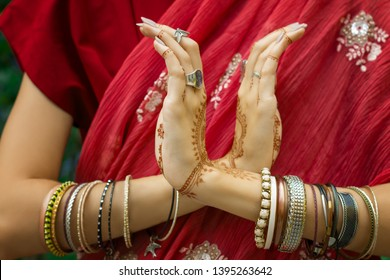Beautiful woman in traditional Muslim Indian wedding pink red sari dress hands with henna tattoo jewelry and bracelets do hands nritta odissi Samyuta hastas dance. Movement nagabanda couple of snakes