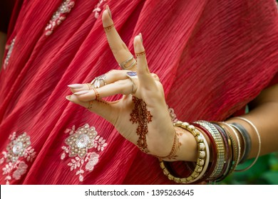 Beautiful woman in traditional Muslim Indian wedding pink red sari dress with henna tattoo jewelry bracelets do hands nritta odissi Samyuta Hasta Mudras dance Movement  Concept background