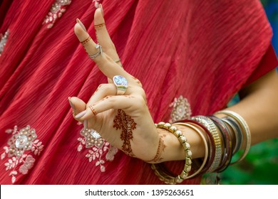 Beautiful woman in traditional Muslim Indian wedding pink red sari dress with henna tattoo jewelry bracelets do hands nritta odissi Samyuta Hasta Mudras dance Movement kartarimukha Concept background