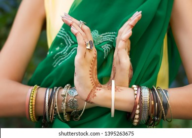 Beautiful woman in traditional Muslim Indian wedding green sari dress hands with henna tattoo jewelry and bracelets do hands nritta odissi Samyuta hastas dance. Movement nagabanda couple of snakes