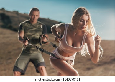 Beautiful  woman with trainer exercising workout outdoors. Young sexy girl doing sports functional training with a man in couple.