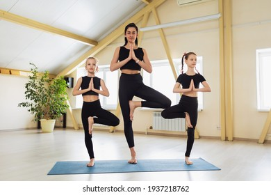 Beautiful woman trainer with two students in black sportswear, practicing yoga, perform Vrikshasana exercise on a gymnastic mat, tree pose with namaste, exercising in a yoga studio.
