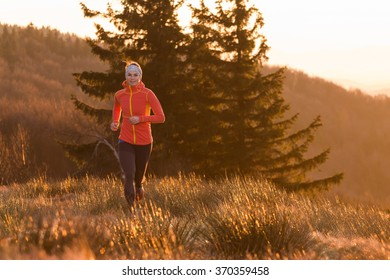 beautiful woman training fitness running in the cold spring morning in the mountains after sunrise