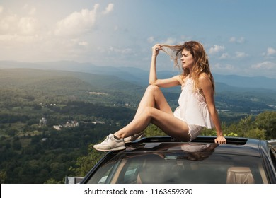Beautiful woman travel by car and enjoy road trip nature view sitting on the roof at summer day