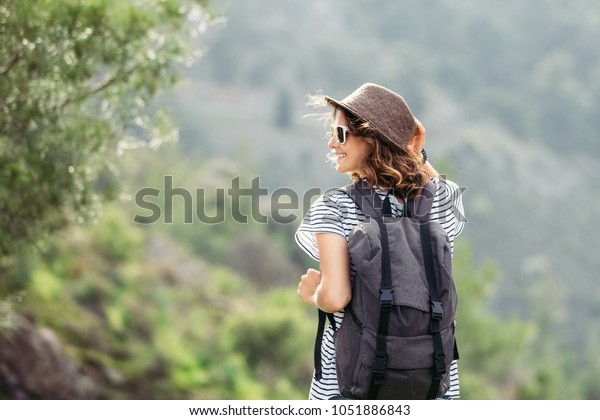 beautiful woman traveler with backpack and in hat on wood background. She is smiling and cheerful, she walks and feels happy and free.