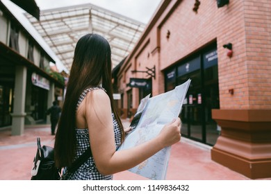 Beautiful woman traveler holding location map in hands while looking for some direction in urban scene in sunny summer day, young female student checking out the sights on atlas during trip overseas