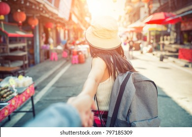 Beautiful woman traveler holding location map in hands while looking for some direction in street food china town.