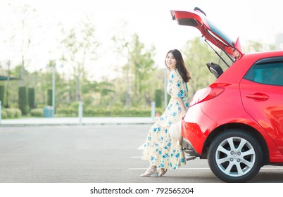 Beautiful Woman traveler sitting on hatchback red car. Travel concept.