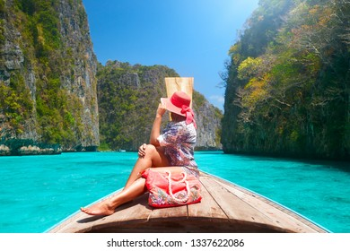 Beautiful woman travelling by boat in summer vacation among the islands Phi Phi and Maya beach in Thailand.