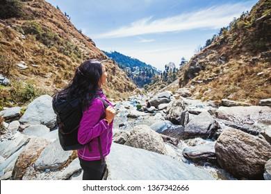Beautiful woman trekking alone in Indian Himalayas. Full length wide angle shot