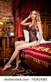 beautiful woman in a trendy black lace body sitting on a chic bed in a castle