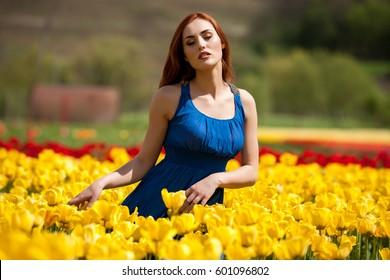 Beautiful woman in tulip flowera field in summer
