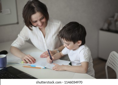 beautiful woman tutor is engaged with a child boy at home at a table, real interior