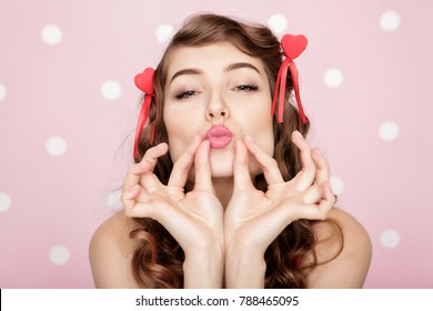 beautiful woman with two red hearts sending air kiss on pink background. St. Valentine's Day.