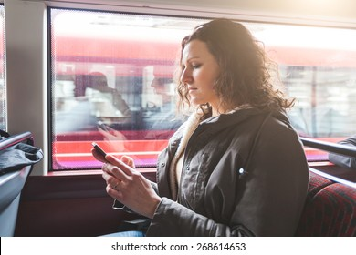 Beautiful woman typing on smart phone while commuting in London with double-decker bus. She is sitting next to the window with buildings and traffic on background.