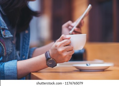 beautiful woman typing text message on smart phone in a cafe