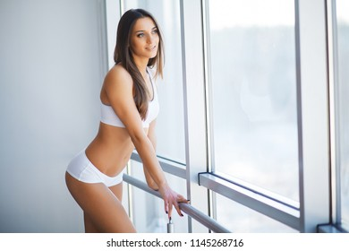 Beautiful Woman in Underwear. Close up Concept. Sexy Alluring Tanned Young Brunette Female Model in Underwear, Posing in White Interior With Panorama Windows on the Background.
