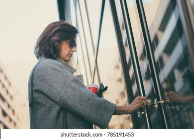 Beautiful woman unlocking door with a key and entering in residential building.