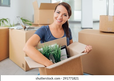 Beautiful woman unpacking a carton box and sitting on her new house's floor, she is smiling at camera