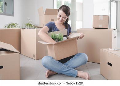 Beautiful woman unpacking a carton box and sitting on her new house's floor, she is surrounded by boxes