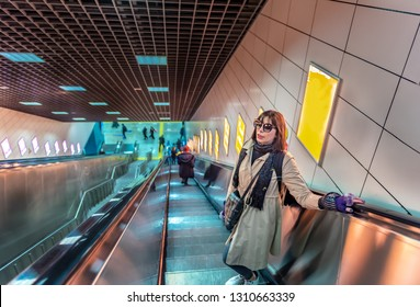 Beautiful woman uses escalator to access Marmaray train in subway metro,Istanbul,Turkey.